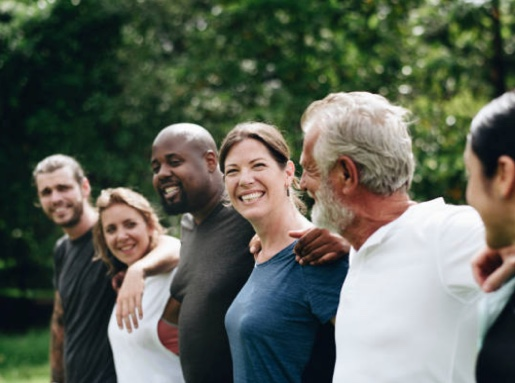 A group of adults outside smile at each other